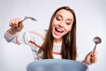 Hungry lady holding fork and spoon cant wait to start eating wear striped pullover isolated white background 스톡 콘텐츠