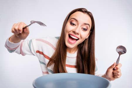 Hungry lady holding fourchette et cuillère a hâte de commencer à manger porter pull rayé fond blanc isolé Banque d'images