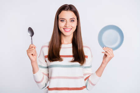 Hungry lady holding spoon and empty plate ready for dinner wear striped pullover isolated white background