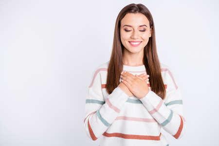 Photo d'une femme incroyable tenant les bras sur la poitrine, les yeux fermés de rêve portent un pull rayé sur fond blanc isolé Banque d'images