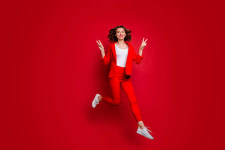 Full body photo of charming woman making v-signs jumping isolated over red background
