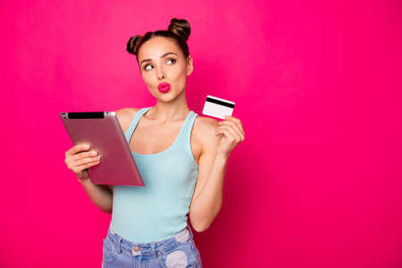 Pretty lady with e-book and plastic card in hands searching show room wear casual outfit isolated bright pink background