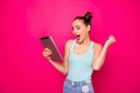 Funny lady with e-reader in hands amazed by sale prices wear casual outfit isolated bright pink background Stock Photo