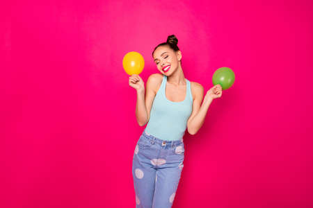 Portrait of charming girl with closed eyes holding small baloon wearing blue singlet isolated over fuchsia background