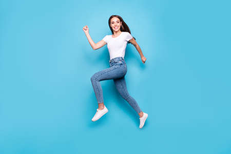 Full length photo of cheerful youth running wearing white t-shirt denim jeans sneakers isolated over blue background