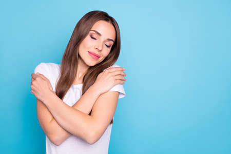 Portrait of cute lady touching her shoulders closing eyes wearing white t-shirt isolated over blue background