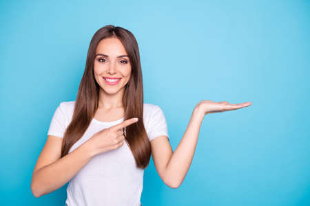 Retrato de hermosa milenaria sosteniendo la mano apuntando a los anuncios con su dedo índice aislado sobre fondo azul.