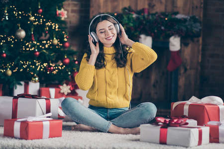 Full length body size photo of rejoicing nice overjoyed girl listening to christmas music rejoicing with new year atmosphere wearing yellow pullover jeans denim sitting on floor