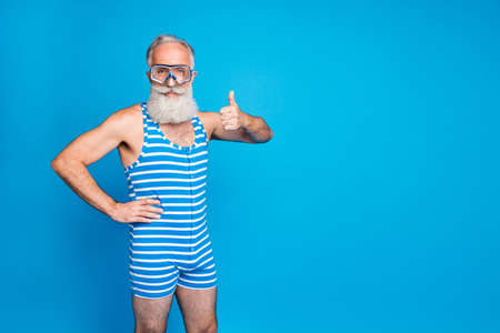 Portrait of joyful pensioner showing thumb up approve sign wearing striped swimwear isolated over blue background Imagens