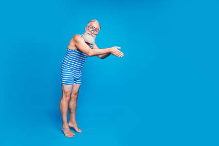 Full size photo of concentrated man jumping into ocean with equipment wearing striped bathing suit isolated over blue background Banco de Imagens