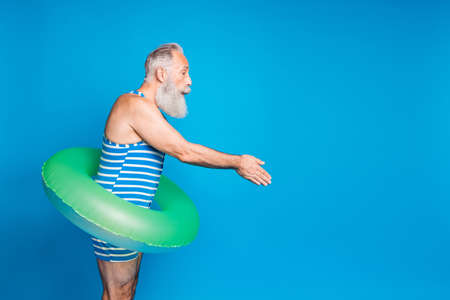 Profile side photo of attractive old man jumping holding lifesaver wearing striped bathing suit isolated over blue background Foto de archivo