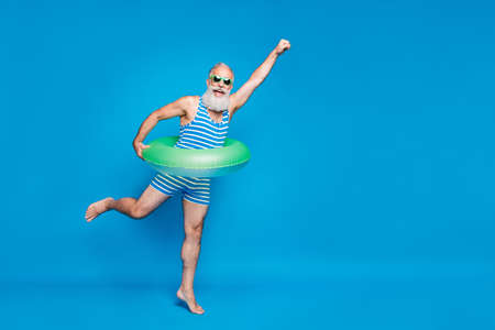 Full length photo of excited retired pensioner with grey hair raising his fist holding toy circle wearing striped swimwear glassses isolated over blue background 版權商用圖片
