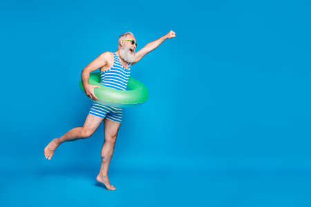 Full body profile side photo of retired pensioner raise his hand running holding green toy ring wear striped bathing suit eyewear eyeglasses isolated over blue background