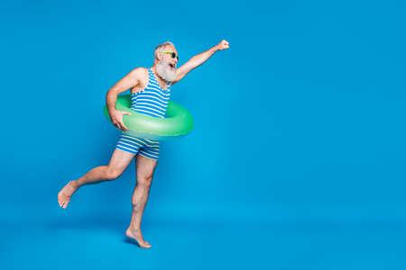 Ganzkörperprofilseitenfoto eines Rentners im Ruhestand hebt seine Hand, die einen grünen Spielzeugring hält, trägt eine gestreifte Badeanzugbrille, die auf blauem Hintergrund isoliert ist isolated Standard-Bild