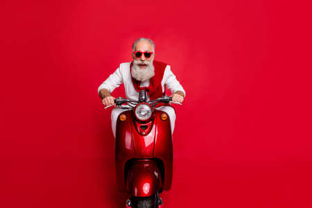 Portrait of funky elderly person in eyewear eyeglasses driving bike screaming wearing white pullover sit ob motor bike isolated over red background