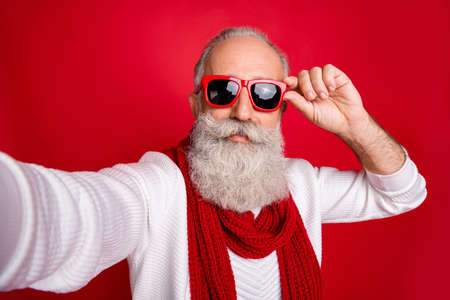 Fashion aged santa man making self photos wear sun specs knitted jumper isolated red background Foto de archivo - 129430884