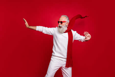 Cool aged santa like man drunk dancing with youth at club wear sun specs knitted clothes isolated red background Stockfoto