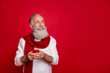 Portrait of his he nice attractive cheerful cheery dreamy gray-haired man holding in hands using cell internet online 5g app isolated over bright vivid shine red background