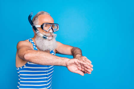 Portrait of retired pensioner swimming breaststroke with snorkel gear wearing striped costume isolated over blue background 免版税图像