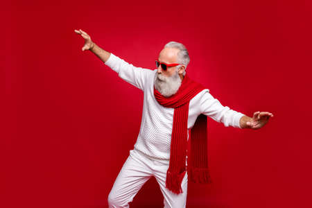 Modern santa character aged man moving like star at party wear sun specs knitted clothes isolated red background