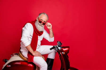 Flirty grandfather santa man sitting on retro moped wear jumper and trousers isolated red background