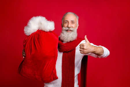 Trendy aged man plays modern santa with large velvet sack raising thumb up wear stylish sweater isolated red background