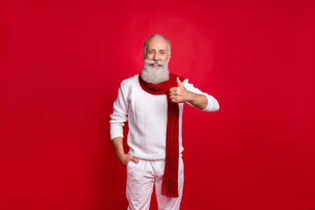 Portrait of retired old pensioner showing symbol thumb up wearing white pullover pants trousers isolated over red background Imagens