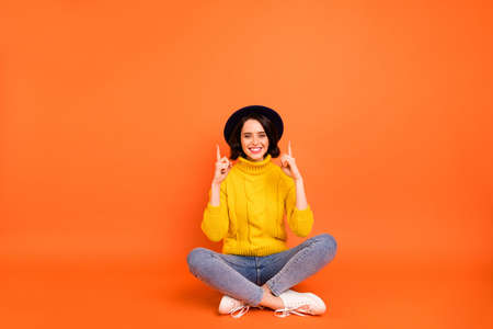 Photo of excited cheerful funny girl pointing up wearing jeans denim headwear cap while isolated with orange background