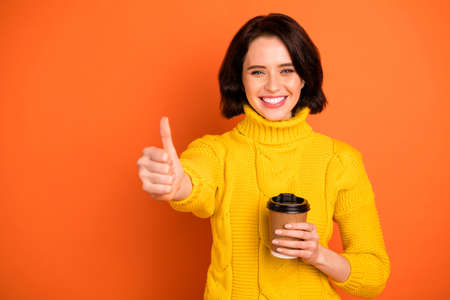 Photo of cheerful nice cute charming pretty sweet girl toothily smiling showing you thumb up sign wearing yellow sweater while isolated with orange background
