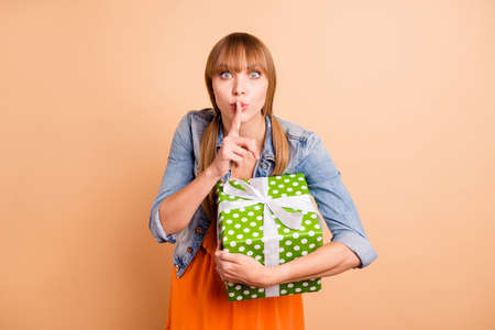 Pretty lady holding large package making surprise for mommy wear casual outfit isolated beige background