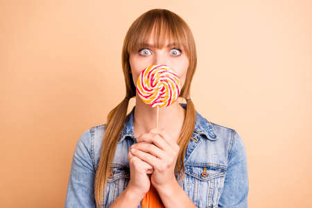 Funky lady hiding mouth with big candy know rumours wear denim blazer isolated pastel beige background