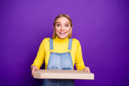 Portrait of cute lady holding pizza screaming wow omg wearing yellow turtleneck denim jeans overalls isolated over purple violet background Stock Photo