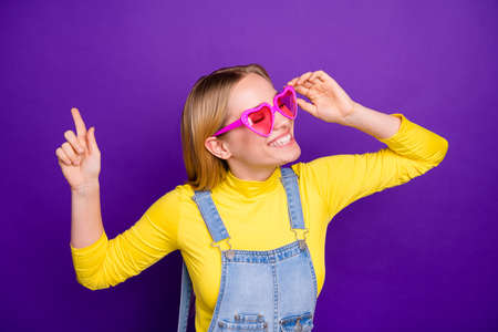 Portrait of cheerful youth touching her specks closing eyes wearing yellow turtleneck denim jeans overalls isolated over purpl violet background