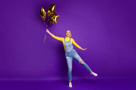 Full length photo of lovely millennial holding baloon wearing yellow turtleneck denim jeans overalls isolated over purple violet background 写真素材
