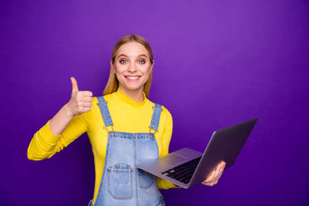 Portrait of cheerful person holding modern technology show thumb up wear yellow turtleneck denim jeans overalls isolated over purple background