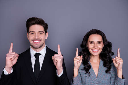 Close-up portrait of his he her she nice attractive stylish cheerful cheery content partners professional experienced experts pointing up ad advert isolated over gray violet purple background