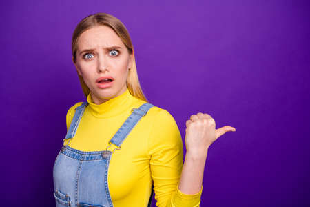 Portrait of impressed youth pointing at copy space wearing yellow turtleneck denim jeans overalls isolated over violet purple background