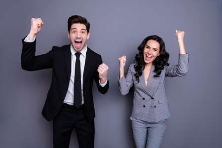 Portrait of ecstatic business people with wavy curly brunette hair raising fists screaming yeah wearing black blazer jacket trousers tuxedo pants isolated over gray background