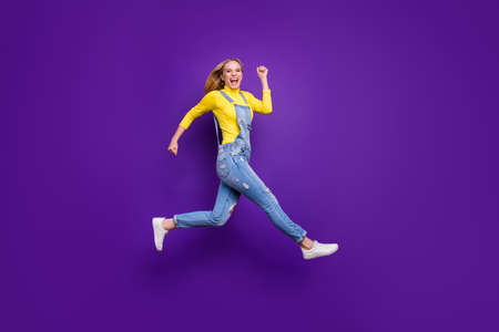 Full length photo of cheerful teenager running screaming wearing yellow turtleneck denim jeans overalls isolated over violet purple background