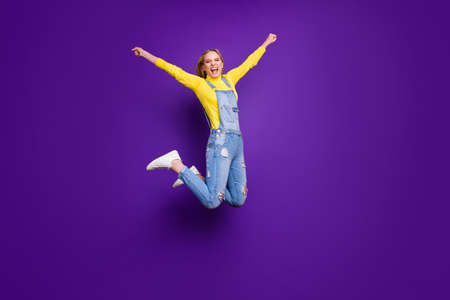 Full length photo of cheerful person screaming yeah raising her hands wearing turtleneck overalls isolated over purple violet background