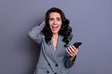 Portrait of amazed person with curly hairstyle touching her head yelling omg wearing jacket blazer isolated over grey background Reklamní fotografie