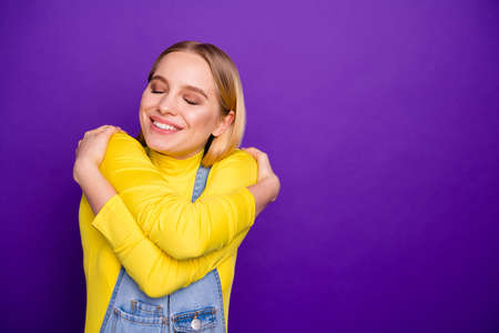 Close up photo of cheerful lady cuddle herself with closed eyes wear yellow turtleneck denim jeans overalls isolated over purple violet background