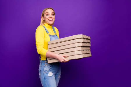Profile side photo of amazed person holding packages with junk food wearing yellow turtleneck isolated over violet purple background