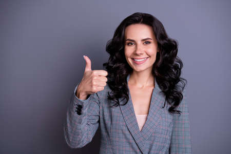 Close up photo of beautiful stylish woman showing her thumb up smiling promoting ads wearing jacket blazer isolated over grey background Imagens