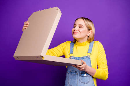 Portrait of content woman with her eyes closed holding pizza smelling wearing yellow turtleneck denim jeans isolated over purple violet background Stock Photo