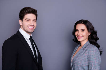 Portrait of beautiful wavy curly brunette haired couple businesspeople looking with toothy smile standing face-to-face wearing black blazer tie jacket isolated over grey background