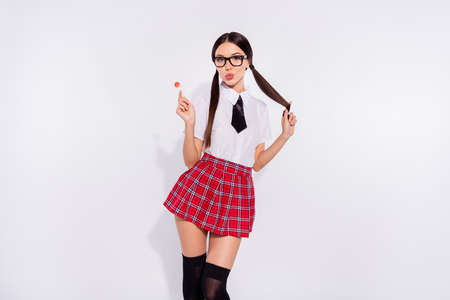 Portrait of her she nice-looking attractive lovely glamorous cheerful cheery, alluring enticing girl wearing checked skirt licking lolly pop isolated on gray light white background Imagens