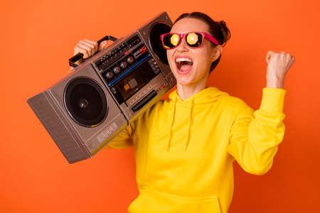 Portrait of cool teenager holding boombox shouting favorite song, dressed eyewear eyeglasses raising fists isolated over orange background Stock Photo