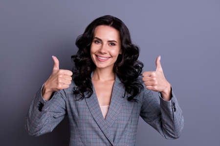 Portrait of cheerful freelancer showing her thumb up promoting ads wearing suit isolated over grey background Imagens