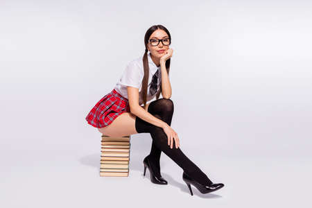 Full length side profile body size photo beautiful model sit book pile diligent student tails return study flirty wear specs short red checkered costume pantyhose isolated white background